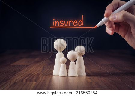 Family life insurance concept. Wooden figurines representing family and hand writing text insured.