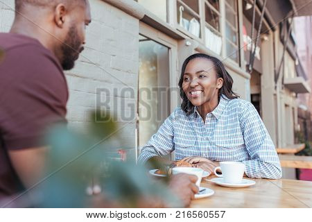 Smiling young African couple sitting together at a table drinking coffee and having a conversation while out on a date at a sidewalk cafe