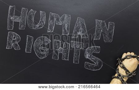 Human rights concept: chained man against the text: Human rights day written with chalk on blackboard.