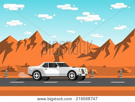 White sedan car rides along an empty highway in the prairies to the backdrop of mountains rocks sky and clouds.