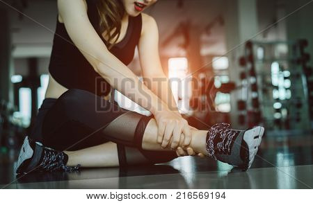 Woman doing sport exercise injury knee accident at gym fitness