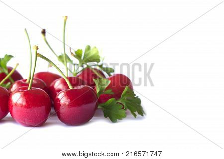 Fresh red cherries lay on white isolated background in side view with copy space. Cherry have high vitamin C and have sweet and sour taste. Red cherry is healthy and delicious fruit. Cherry on white isolated background concept.