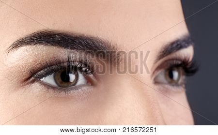 Beautiful young woman with eyelash extensions on grey background, closeup