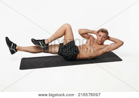 Muscular shirtless sportsman lying on mat doing abdominal twist exercise on white studio background.