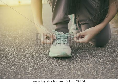 Female runner tying her shoes preparing for jogging outside .Young girld runner getting ready for training. Sport lifestyle