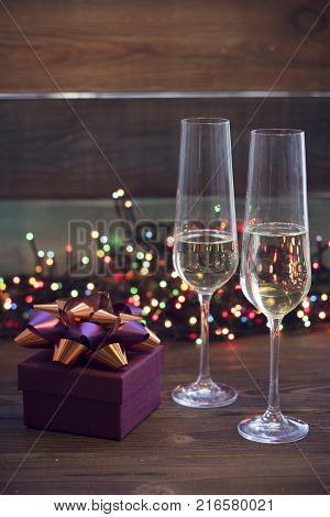 Two glasses of champagne and a burgundy gift box with a green and purple shiny bow on a table.Dark colored wooden background. Christmas fairy lights on the back. Dark colorful bokeh