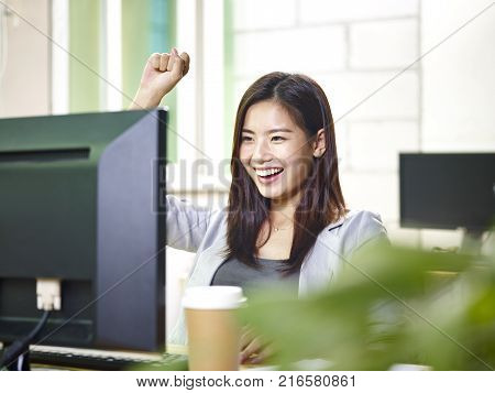 young asian business woman working in office using desktop computer happy and excited at good news.