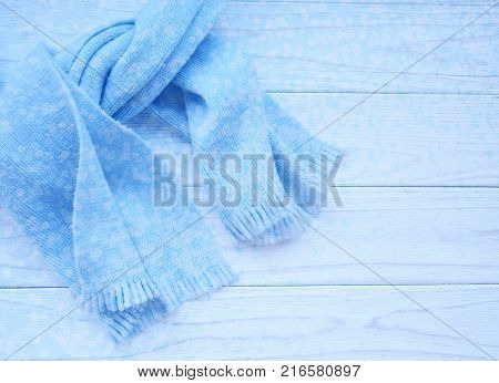 Light blue scarf tied up on a wooden background (copy space on the right beautiful blurred blue festive bokeh in the front) as a New Year Christmas or winter background