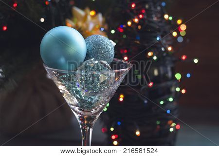 Festive still life with a glass filled with shiny blue balls and a bottle wrapped up in garland. Dark rustic wooden background. Close up. Blurred bokeh