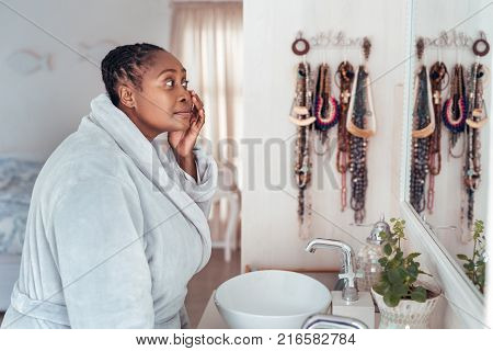 Young African woman wearing a robe standing in her bathroom in the morning looking at her complexion in the mirror