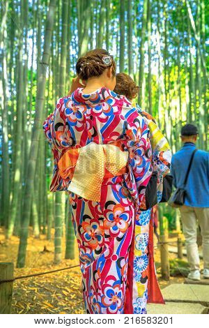 Unidentifiable women with Japanese kimono walking in bamboo grove of Take-dera or Hokoku-ji Temple in Kamakura, Japan in Hanami season. Japanese culture and lifestyle.