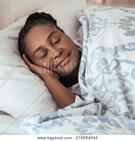 Square image of content young African woman sleeping peacfully under a duvet in her bed at home in the early morning