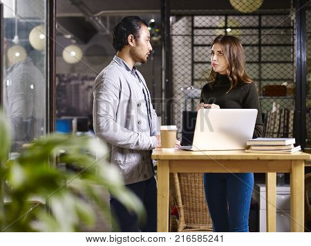 asian businessman and caucasian businesswoman meeting in office discussing business using laptop computer.