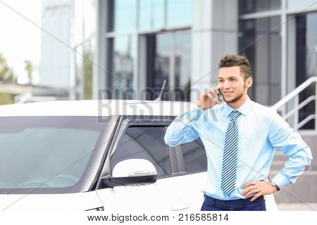 Salesman talking on phone near new car outdoors