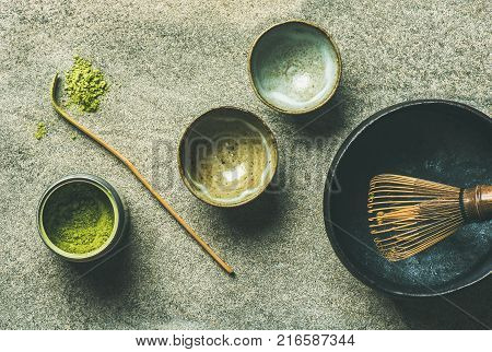Flat-lay of Japanese tools for brewing matcha green tea. Matcha powder in tin can, Chashaku spoon, Chasen bamboo whisk, Chawan bowl and cups over grey background, top view
