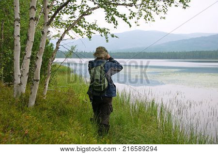 Traveler taking pictures of a forest lake.