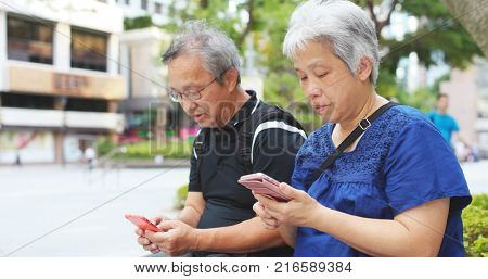 Asian elderly couple use of cellphone together