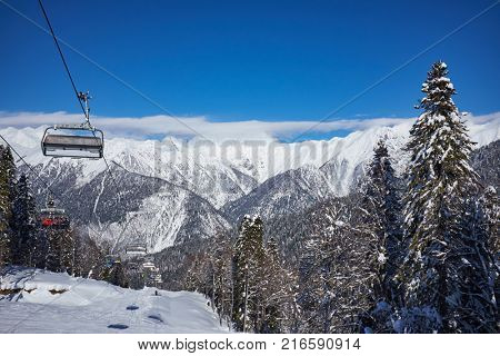 Skiers on the chairlift - ski resort during winter sunny day