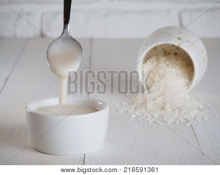 White homemade natural raw organic coconut butter, cream or urbech - healthy raw vegan food. Natural nut paste from coconut. Dagestani useful delicacy. Dry coconut on background.