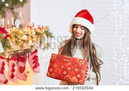 Shot of a cheerful young brunette woman wearing Christmas hat posing with a present in her hands expressive people lifestyle recreation festive event party celebrating x-mas holidays. 2018