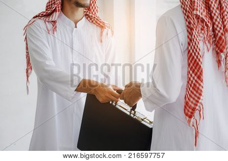 Arabian business man transfer deal after finishing up a business meeting in office handover of a briefcase in hand of partner successful meeting partner teamwork community connection concept