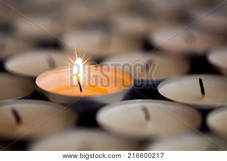 Selective focus on shining magical light of a single sparkling flame from one candle among many extinguished tealight candles. Christmas or celebration image of beautiful star flaming candlelight
