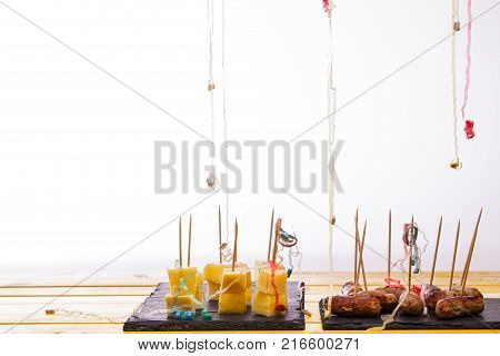 Party food leftovers. Cheese and pineapple and cocktail sausages on sticks. Leftover nibbles with party popper streamers in front of white background with copy space.
