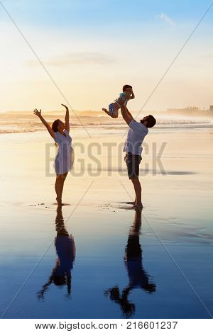 Father tossing high in air baby son mother jumping by water pool. Happy family walk with fun by sunset black sand beach with sea surf. Active parents outdoor activity on summer vacation with kids.