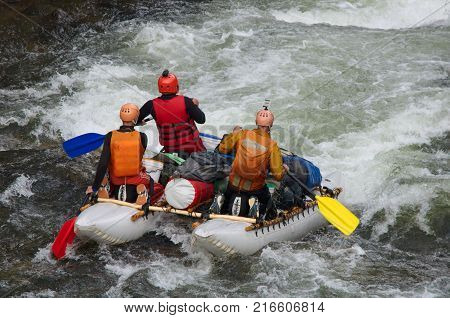Team of athletes on an inflatable catamaran rafting on white water. Chaya river, North Baikal Highlands, Siberia, Russia.