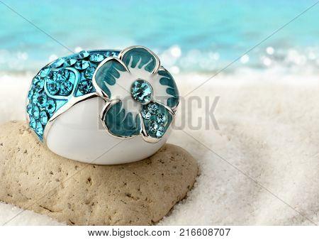 Jewelery ring with gems on sand beach
