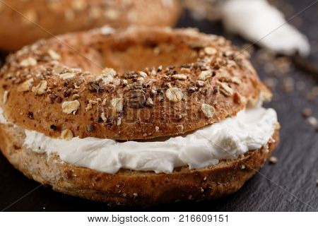 Bagel sandwich with soft cheese on a slate cutting board