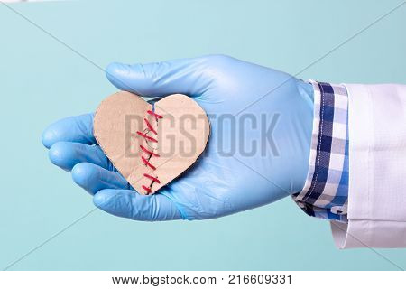 The operation on the heart was successful the heart was cured. Doctor holding a heart