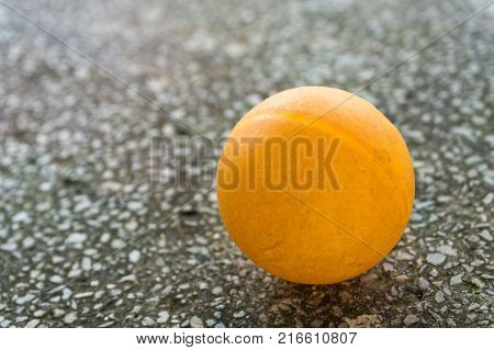 Orange ping pong on the floor.Orange ball place on the table with blue floor between Two Table Tennis paddle or Ping Pong racket, Sport Equipment Concept