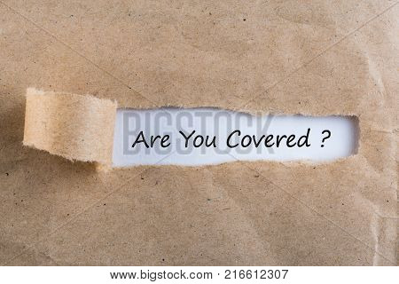 ARE YOU COVERED Question message appearing behind ripped brown paper. Are you insured for your car, travel, home, health or other liability.