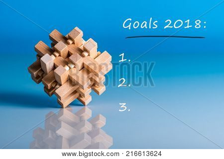 Goals 2018. To do list for next year. Memo at blue background with wooden brain teaser.