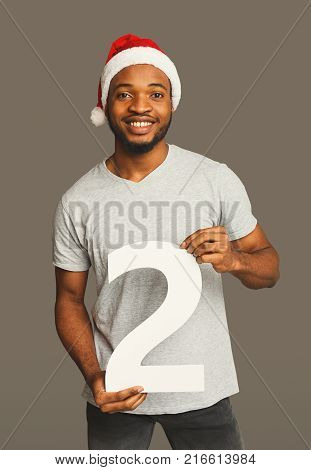 Happy black man with 2 number portrait. African-american boy in santa hat at studio background. One of shots to compose 2018 for new year and christmas greeting card