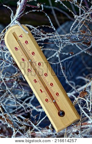 brown wooden thermometer on the winter street on the branches of plants in frost and snow