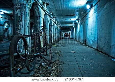 Gritty dark Chicago city street under industrial train bridge viaduct tunnel with bicycle and person at night.