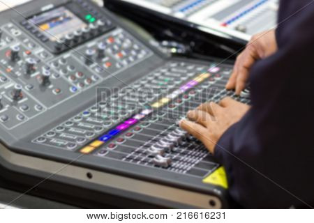 Blurred - hands of Men are controlling the console of a large hi-fi system. Sound equipment. Control panel of a digital studio close-up mixer.