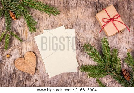 Empty sheets on wooden background. Christmas decorations with gift and fir tree. Preparing for Christmas list of gifts.