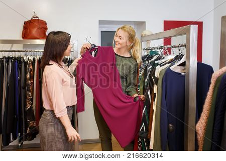 sales consultant helping chooses dress for the customer in the store. Shopping with stylist. Beautiful female shop assistant consulting young woman in the fashion boutique