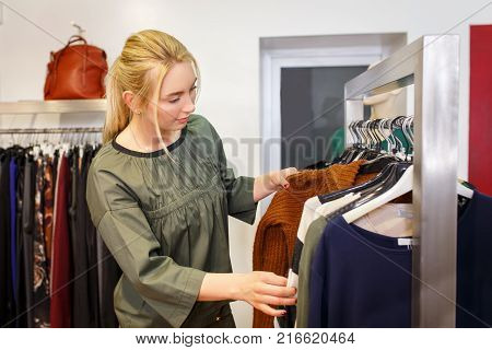 young woman chooses clothes in the store. Shopper near clothes rack in fashion boutique. Shopping concept