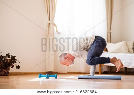Active senior man doing exercise at home. Man next to a wheelchair doing frogstand. Knees on elbows.