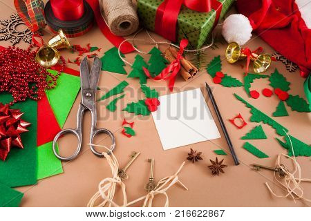 Creative diy craft hobby. Decoration of greeting card for Christmas on messy table with felt sheets and scraps, scissors and trappings at craft paper background. Home leisure, holiday decorations.