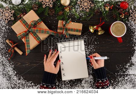 Holiday decorations and notebook with wishlist on rustic wooden table with gift boxes and fir branch sprinkled with snow. Top view, preparing for winter holidays concept.