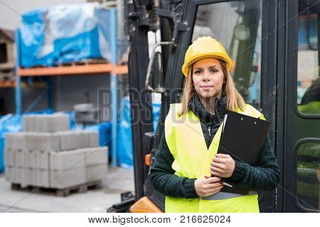 Woman forklift truck driver in an industrial area. A woman standing in front of the fork lift truck outside a warehouse.