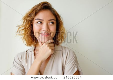 Portrait of uncertain young Asian woman wearing dress touching chin, smiling and looking away. Expression concept