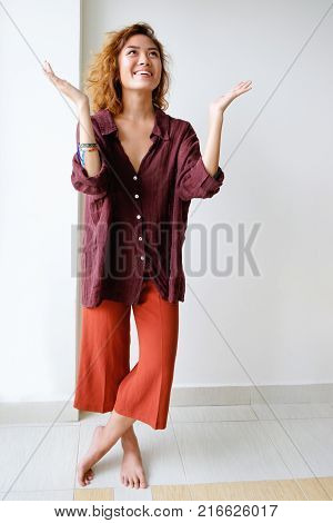 Portrait of young Asian woman wearing pajamas standing barefoot and raising hands in praising gesture