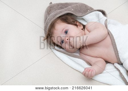 Cute baby girl lying on a white bed blanket and keeps fingers in his mouth. Happy childhood concept. Baby sucking fingers looking at you. Little three months old kid lying with fingers in the mouth.