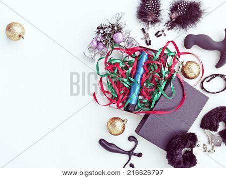 Blue vibrator in a gift box with colored ribbons. Around the gift are Christmas decorations. Image for the festive season, for sales and discounts in sex shops. There is a space for text